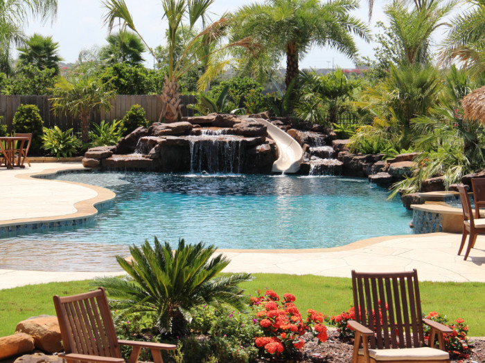 Pool with a waterfall, cave, and slide. Many plants and chairs surround the pool.